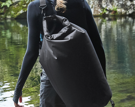 WOMAN HIKING WITH BLACK TECHNICAL RUCKSACK